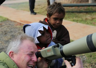Staff member teaching children how to use a telescope