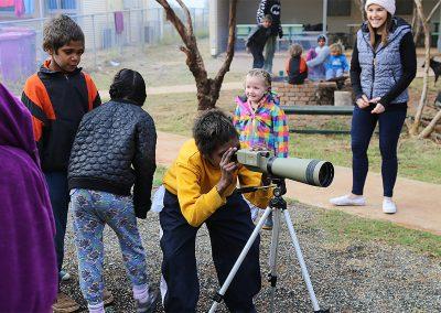Children in looking through a telescope